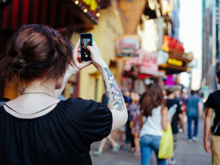 Female taking a photo of a crowded city street