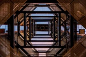 Looking up through several stories of metal scaffolding and framing