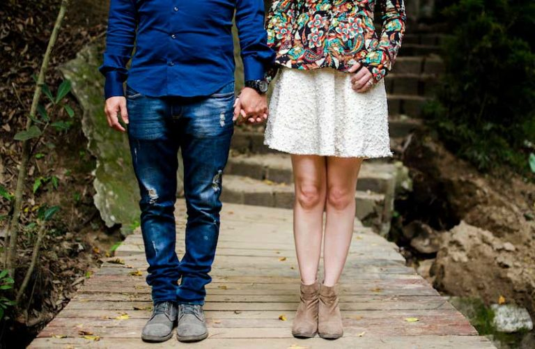 Couple standing on a dock holding hands