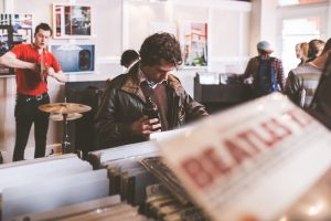 Male with a beer browsing at a record store