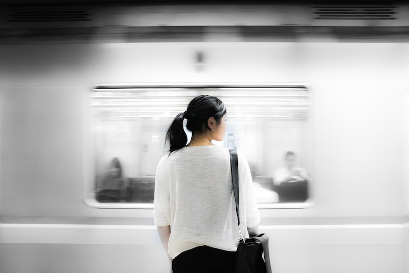 Female standing in front of a moving train