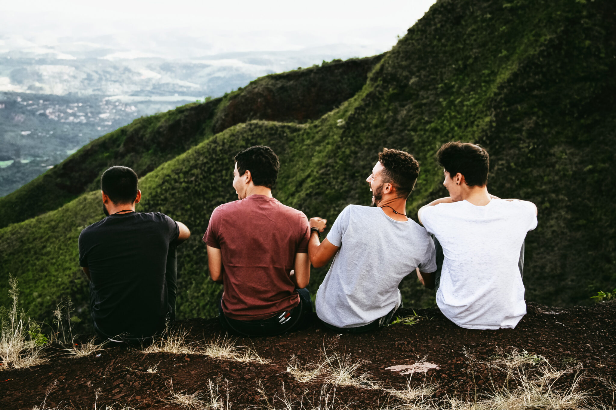 four friends sitting looking over a valley, calm because they have a bank account that helps them.