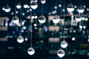 Several spherical bulbs hanging in front of a blurred cityscape