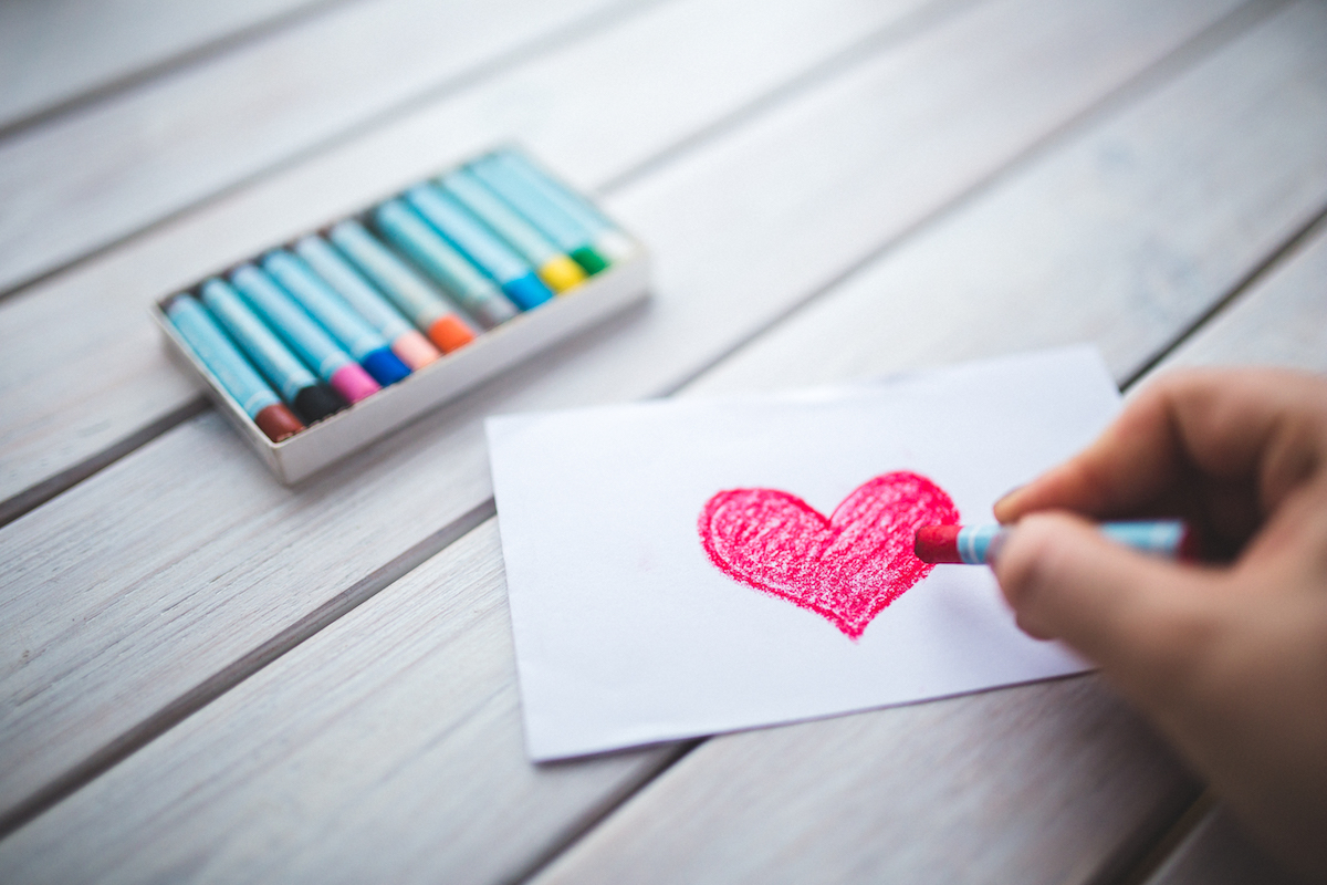 Drawing a heart with crayons on a table
