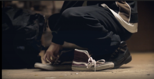 Person kneeling next to empty shoes on a street