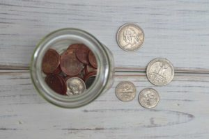 Jar of change with loose change on table
