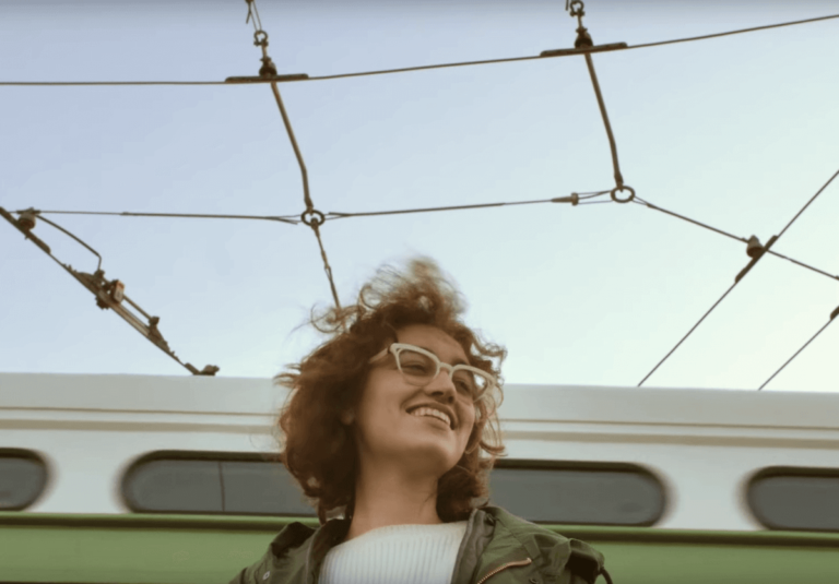 Smiling female in front of a bus