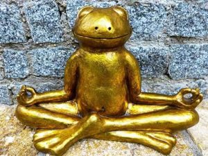 Golden statue of a frog meditating