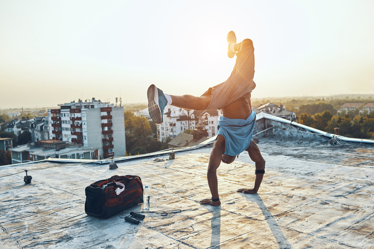 Man doing a handstand on the roof of a building