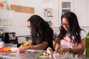 Two females chopping vegetables in a kitchen