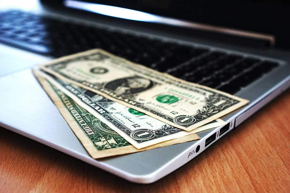 Three one dollar bills on a laptop computer