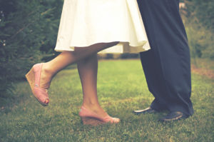 Legs and feet of a couple standing in grass