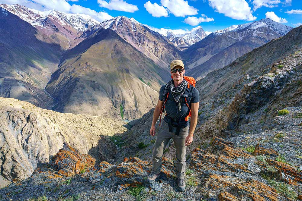 Younger adult male hiking amongst large mountains