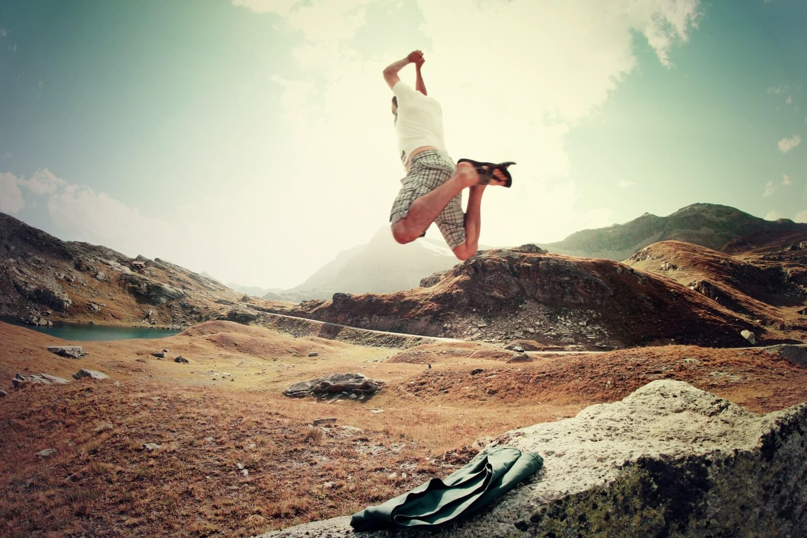 Man jumping for joy off a rock in the wilderness
