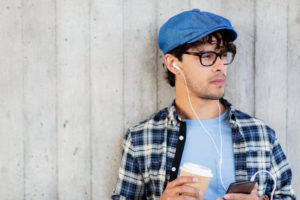 Younger adult male with cell phone and a coffee