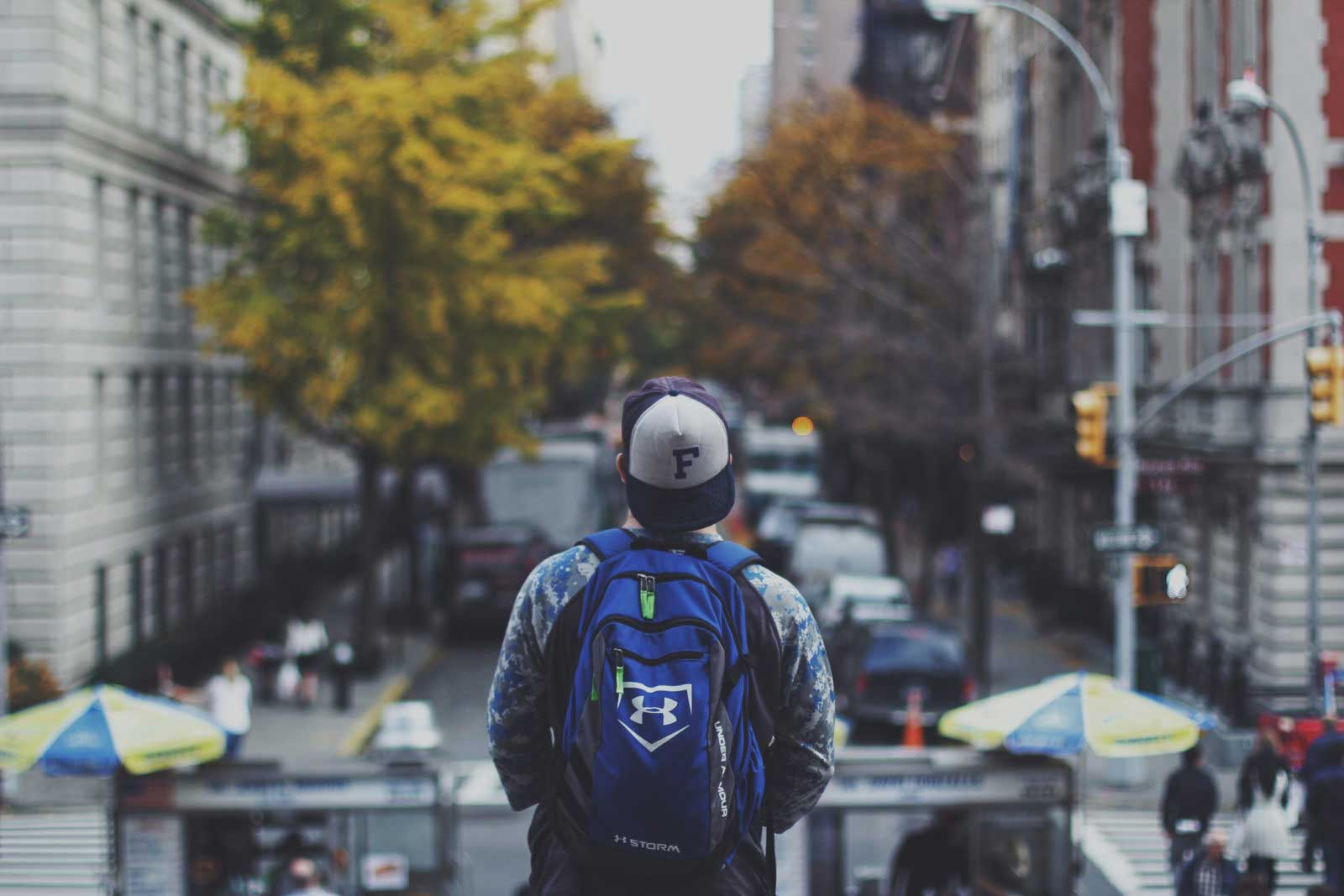 Male with a backpack staring down a city street