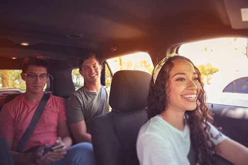 Three smiling young adults inside a car