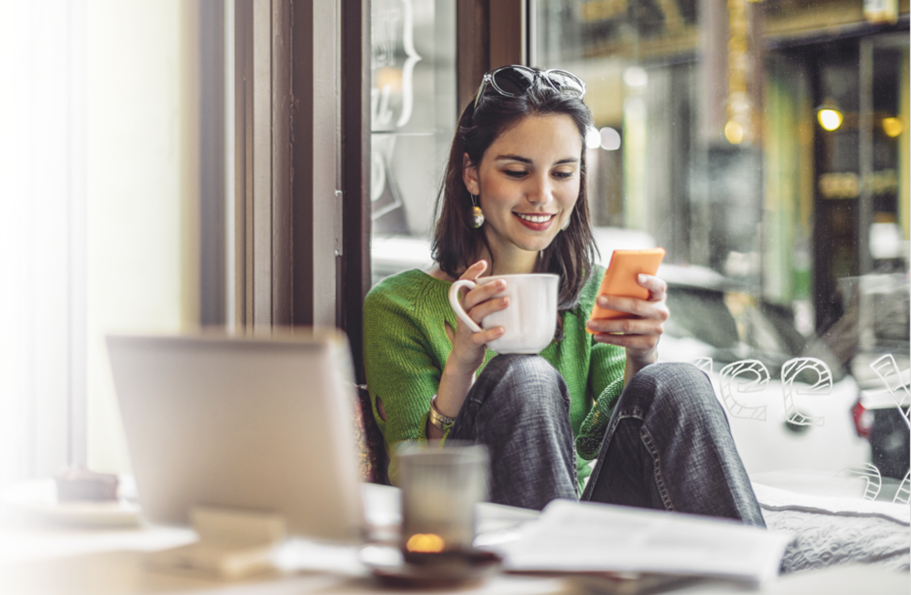 Female drinking coffee while mobile banking with Varo