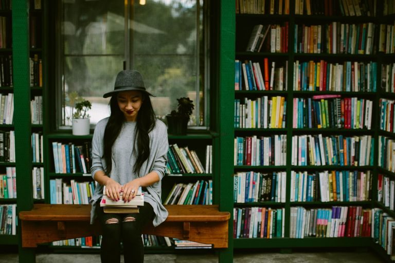young girl sitting on bench wearing ripped jeans and a hat, holding a stack of books on her lap.