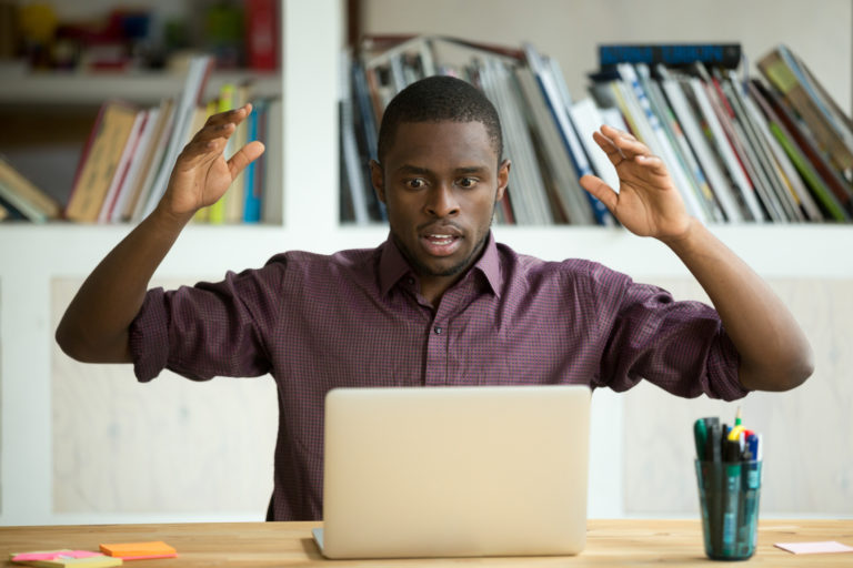 Stunned male with hands up staring at a computer