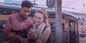 Young couple smiling at a phone at a train station