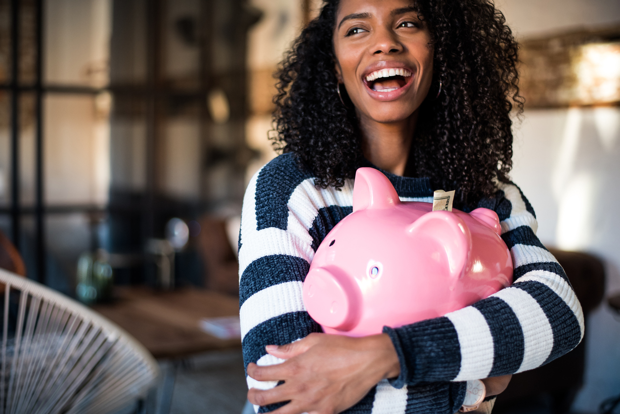 Smiling female holding a piggy bank