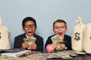 Two screaming young boys surrounded by money and wearing glasses