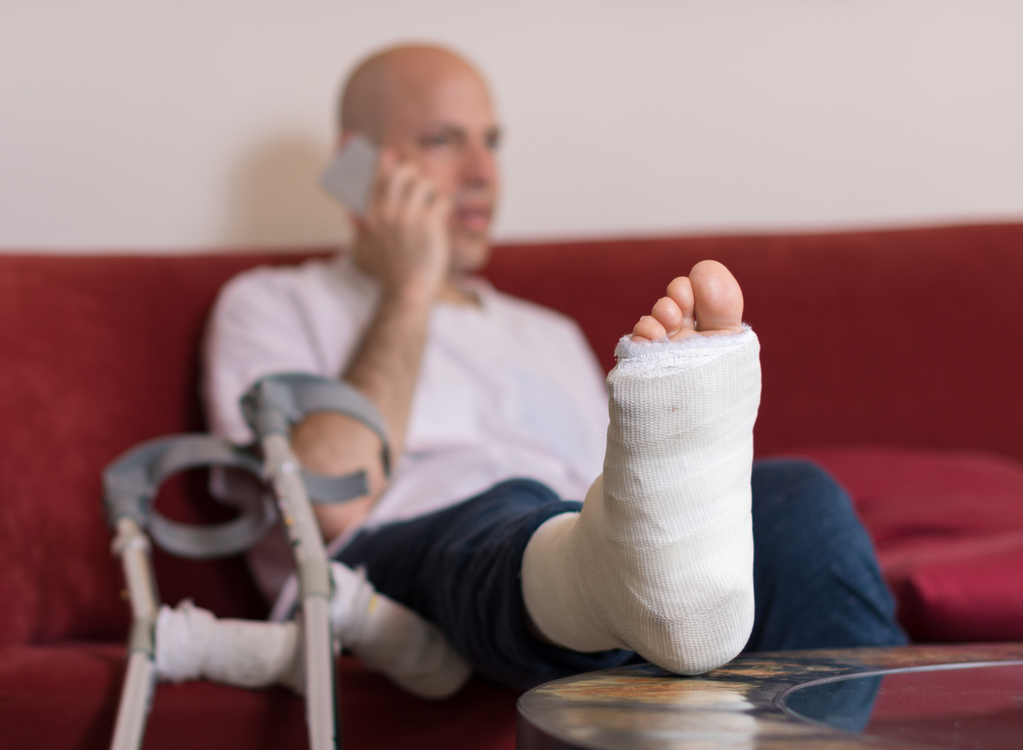 Injured male sitting on a couch and talking on a cell phone