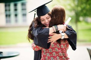 Female recent graduate hugging another female