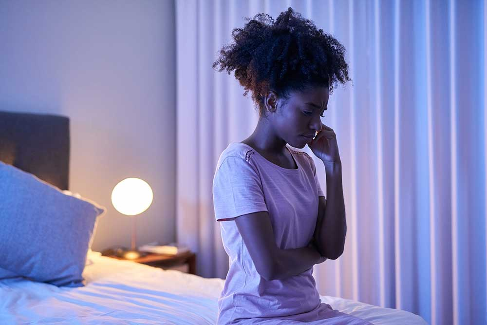 Worried female sitting on the edge of a bed