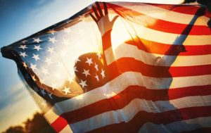 Two people holding an american flag at sunset