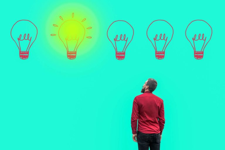 Man staring up at an illustrated lit up light bulb
