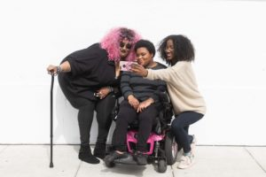 Two females taking a selfie with a third female in a wheelchair