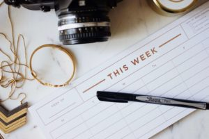 Assorted items and a weekly planner on a table