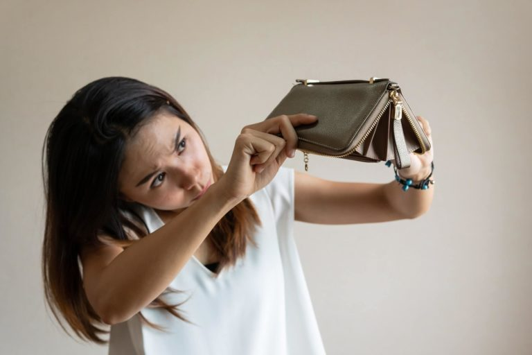 Female holding an empty purse upside down