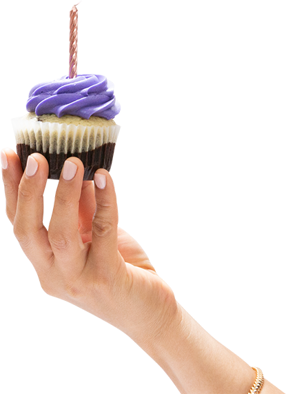 Hand holding a cupcake with one birthday candle
