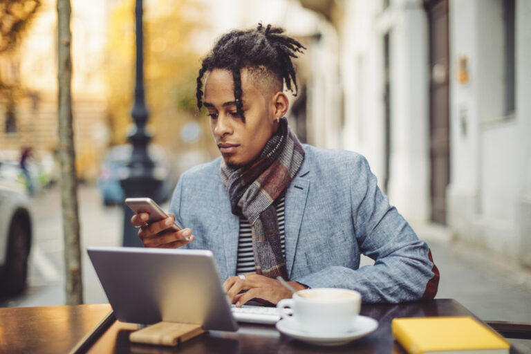 Young adult male at a coffee shop mobile banking with Varo
