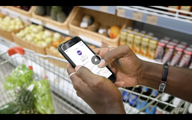 A person using Varo mobile banking at the grocery store