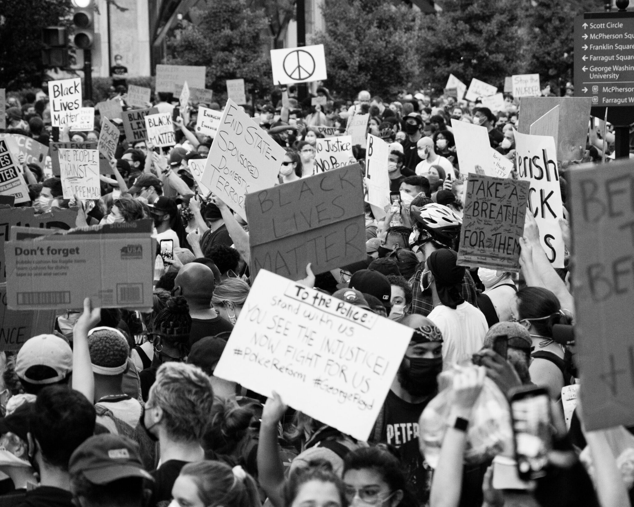 A crowd of people holding signs at a black lives matter protest