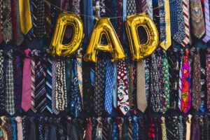 Balloons spelling DAD in front of many ties