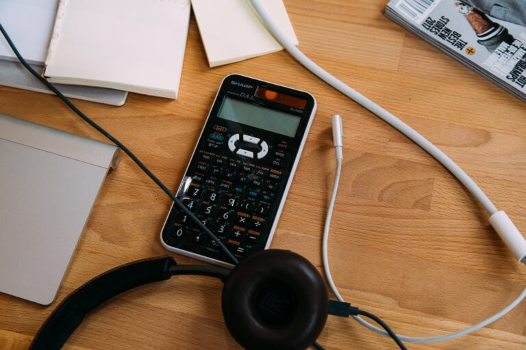 Headphones, a calculator and notepads on a desk