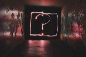 A dark hallway with a question mark formed with light