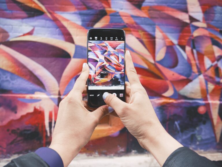 A person taking a photo of a multi-colored mural on their phone