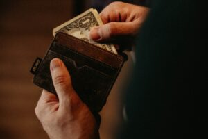 A person pulling a one dollar bill out of a wallet