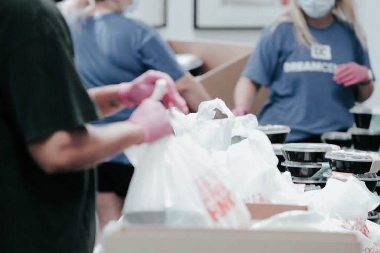 Food workers preparing meals and putting them in plastic bags