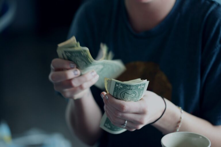 A person counting a stack of one dollar bills