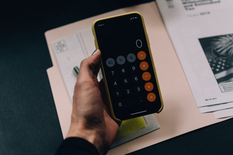 A hand holding up an iPhone showing the calculator app