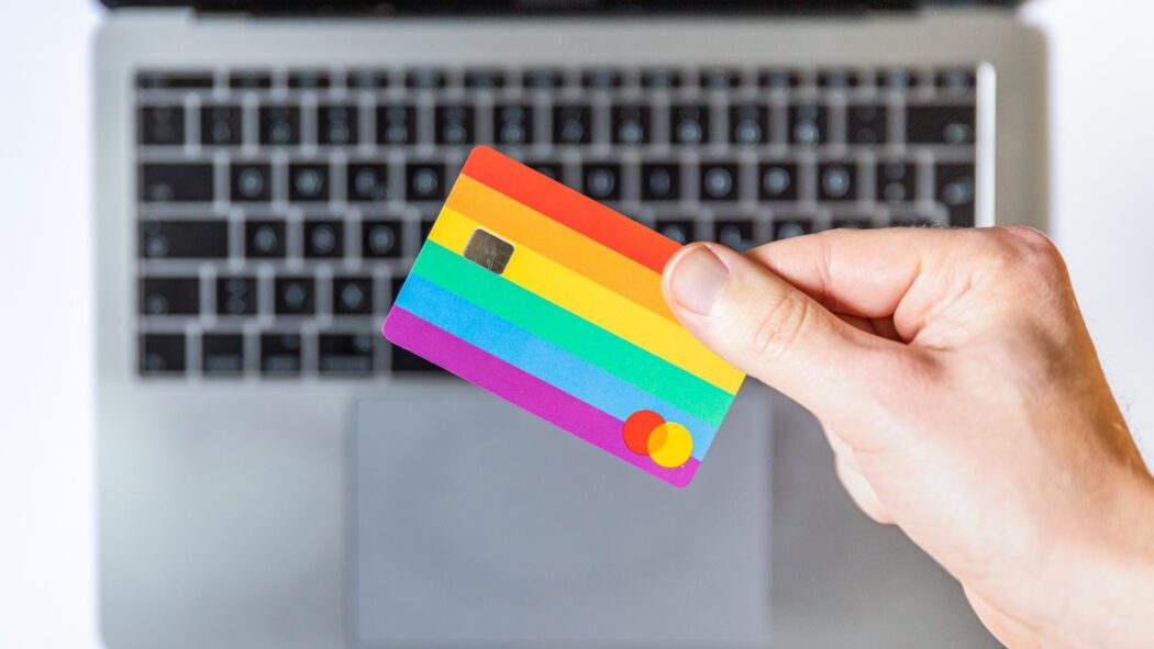 A hand holding a multi-colored credit card above a laptop