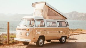 A peach colored Volkswagen bus with its top popped up