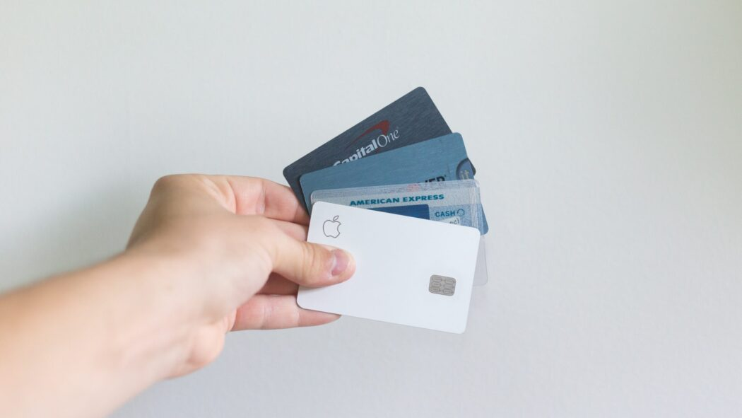 A hand holding four different credit cards